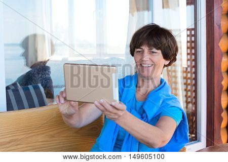 Happy woman taking selfie with tablet pc in cafe. Woman relaxes after travel and enjoying impression shares emotions with friends via Internet.