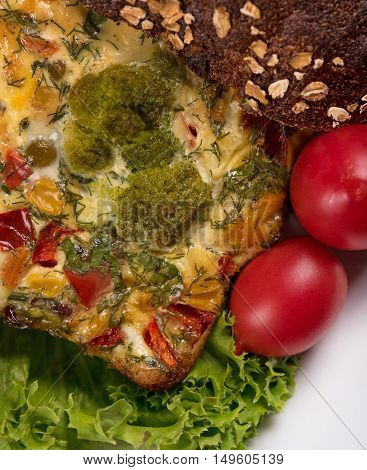 Vegetable baked pudding with bread and tomatoes on the plate