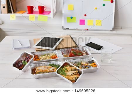 Healthy daily ratio for diet, foil boxes of meat and vegetables with water glass on working table in office. Workspace with mobile phone, papers and tablet.