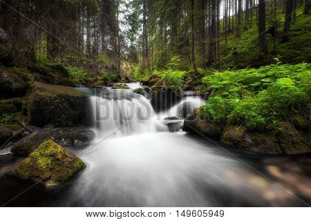 Amazing waterfall flowing between large rocks in a deep green forest at Low Tatras National park Slovak Republic.
