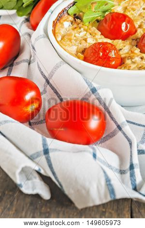 Casserole With Zucchini, Tomatoes And Greens On A Napkin On A Wooden Table