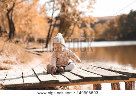 Baby girl 1 year old playing in autumn park. Wearing trendy knitted clothes outdoors.