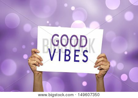 GOOD VIBES card in hand with abstract light background. Selective focus.
