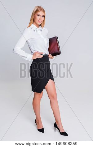 Young businesswoman working at laptop computer. in full growth in office clothes girl. she smiles and contented