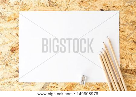 Bunch Of Pencils With Sharpener, On Blank White Sheet Of Paper, On Flakeboard
