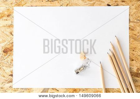 Bunch Of Pencils With Sharpener And Pencil Shavings, On Blank White Sheet Of Paper, On Flakeboard
