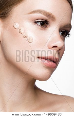 Beautiful young girl with tone cream on her skin. Beauty face. Picture taken in the studio on a white background.