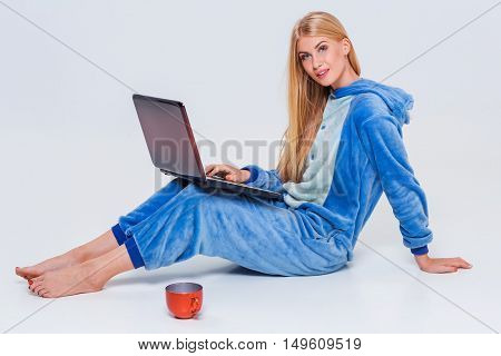girl in pajamas with a laptop lying on the floor. studying or doing online shopping. work from home. Satisfied and smiling