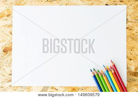 Bunch Of Colorful Pencils, On Blank Sheet Of Paper, On Wooden Surface