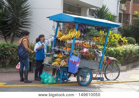 Lima, Peru - September 17, 2015: A lady selling fruit to customers on the street with her fruit bicycle