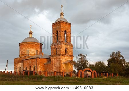 Antique Russian orthodox cathedral building against sky with clouds. Autumn evening before sunset.