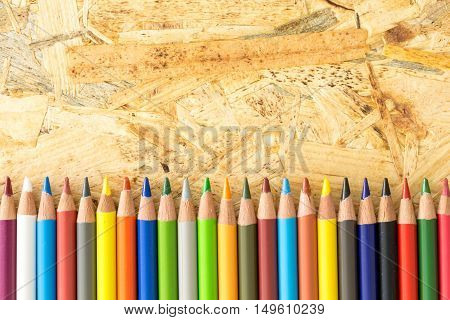 Bunch Of Colorful Pencils, On Flakeboard Surface With Copy-space.