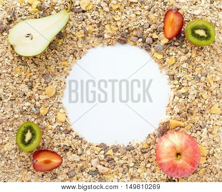 Muesli cereals a mixture of healthy grains cereal flakes and dried fruits spread out on a white background with fresh apple plum kiwi and pear placed on top. Copy space in the round middle.
