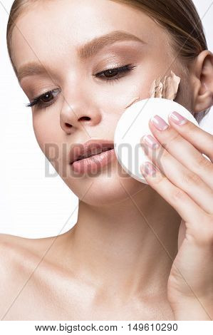 Beautiful young girl with sponge for application make-up and French manicure. Beauty face. Picture taken in the studio on a white background.
