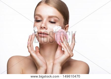 Beautiful young girl with sponge and foam cleanser and French manicure. Beauty face. Picture taken in the studio on a white background.