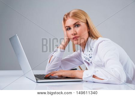 Young businesswoman working at laptop computer. tired, hunched, pleased