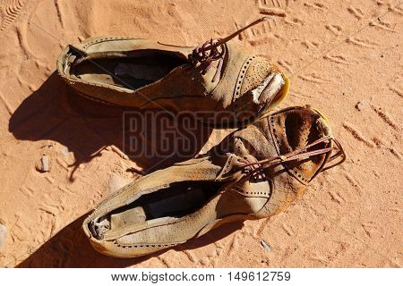 old dirty pair of shoes on sand background