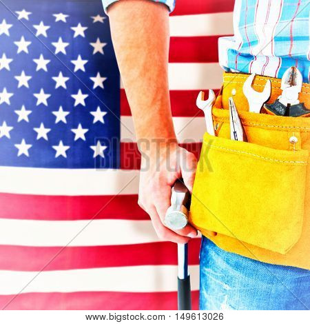 Handyman wearing tool belt while holding hammer against rippled us flag