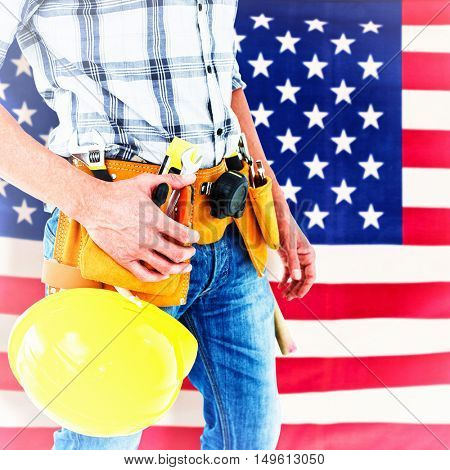 Technician with tool belt around waist and hard hat against rippled us flag