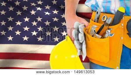 Manual worker wearing tool belt while holding gloves and helmet against close-up of american flag