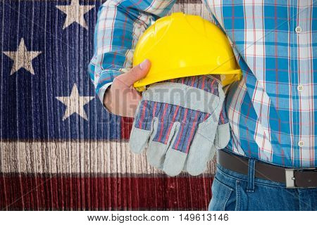 Construction worker holding hard hat and gloves against composite image of usa national flag