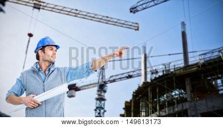 Architect pointing against crane and building construction site