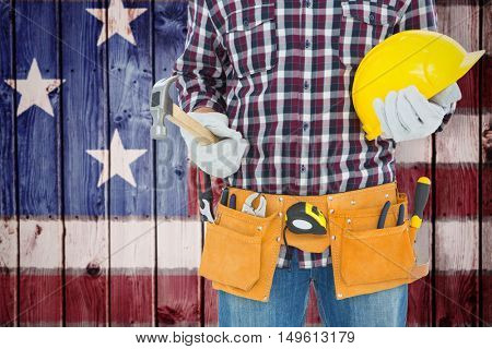 Handyman holding hard hat and hammer against composite image of usa national flag