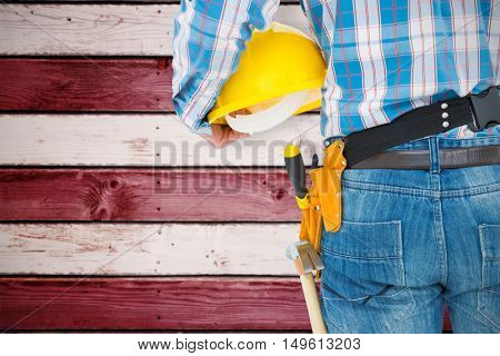 Rear view of handyman wearing tool belt against composite image of usa national flag