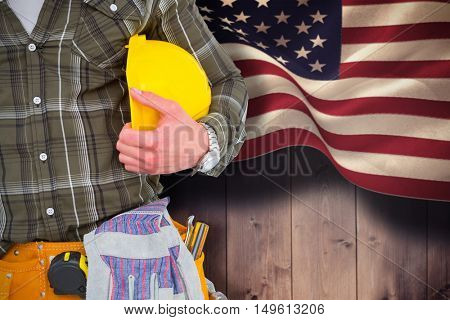 Manual worker wearing tool belt while holding helmet against composite image of digitally generated united states national flag
