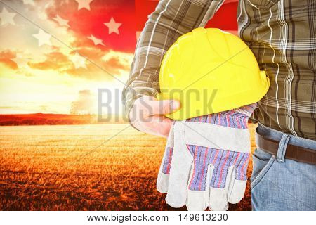 Manual worker holding helmet and gloves against american flag rippling over landscape during sunrise