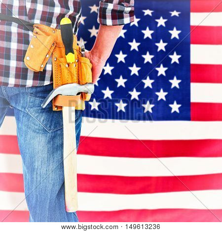 Cropped image of handyman wearing tool belt against rippled us flag
