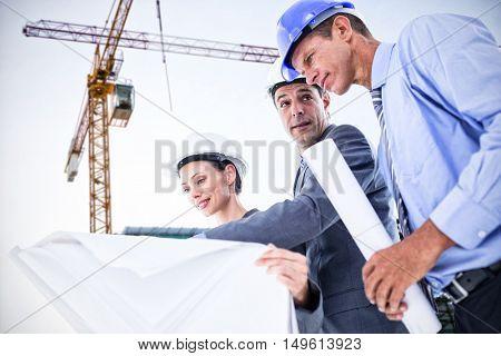 Businessman explaining a blueprint to his colleagues against crane and building construction site