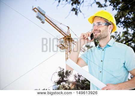 Male architect with blueprint talking on mobile phone against view of a crane