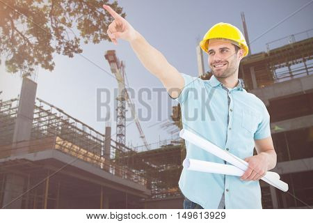Male architect with blueprints pointing away against image of construction site