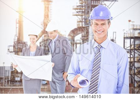 Businessmen and a woman with hard hats and holding blueprint against image of factory