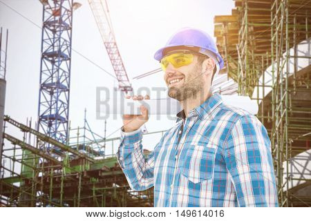 Smiling architect looking away while holding blueprint against work in progress in the city