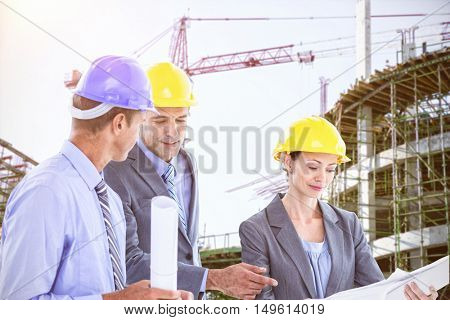 Businessman explaining a blueprint to his colleagues against work in progress in the city