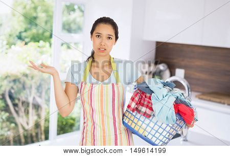 Puzzled young woman holding laundry basket full of dirty laundry against empty modern kitchen