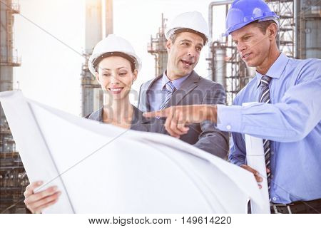 Businessmen and a woman with hard hats and holding blueprint against view of industry