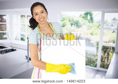 Cheerful woman wiping down white surface against empty modern kitchen