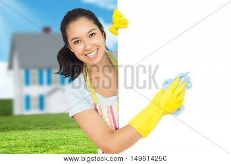 Cheerful woman cleaning white surface against house in the distance