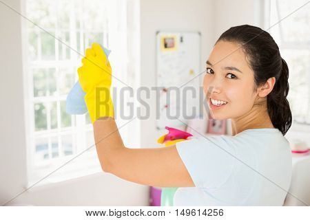Smiling woman cleaning walls against bedroom