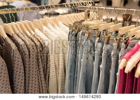 Womens clothes and jeans are hanging on hangers in a store