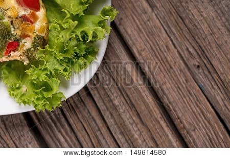 Vegetable baked pudding with green lettuce on the wooden surface with empty space for text