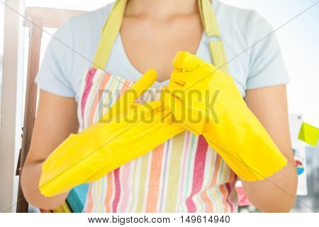 Woman taking off her rubber gloves against business stuffs laying on wooden scale
