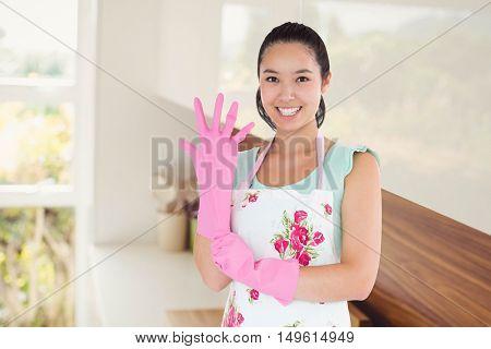 Woman putting on plastic gloves against room full of shelves
