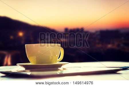Cup of coffee and tablet pc against view of the city by night