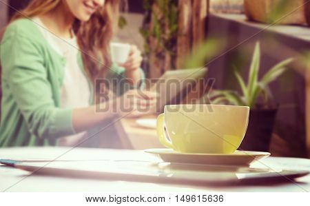 Cup of coffee and tablet pc against smiling woman drinking coffee and using tablet