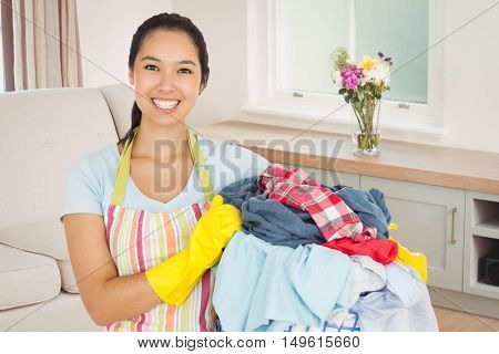 Laughing woman holding laundry basket against sitting room