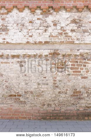 Broken old bricklaying wall from red white bricks with damaged plaster and road pavement background texture in the oldtown street
